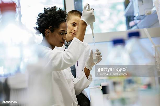 Female scientists pipetting in a laboratory