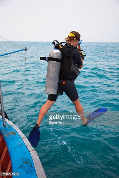 Female Scuba Diver Jumps In Water; Koh Tao, Thailand
