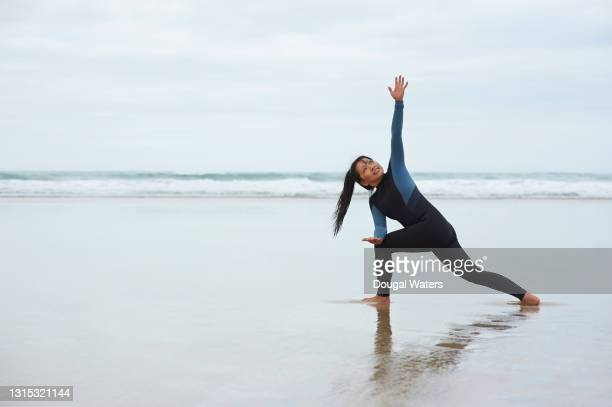 female sea swimmer on beach preparing to swim in sea. - dougal waters stock pictures, royalty-free photos & images
