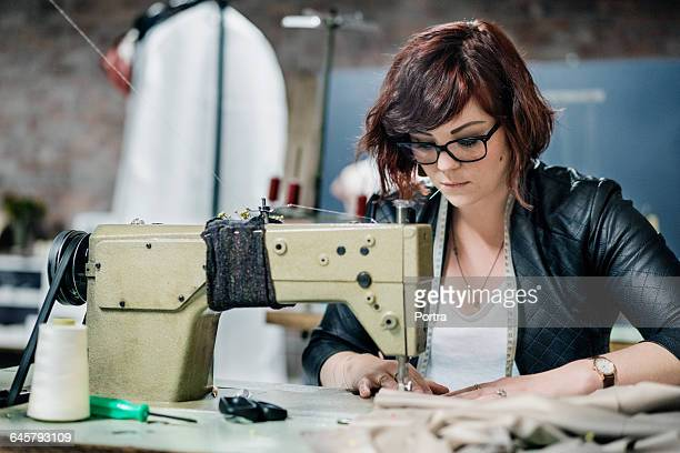 Female seamstress working on sewing machine