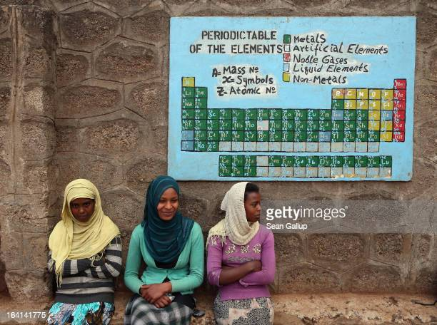Female secondary school students sit under the periodic table of the elements in the courtyard at the AGOHELD orphanage hospital training center and...