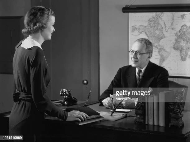 Female secretary standing before her male manager who sits behind his desk, a world map hangs on the wall behind him, circa 1945. On the desk is are...