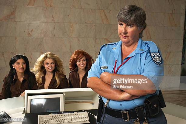 Female security guard with arms folded, three women at desk behind
