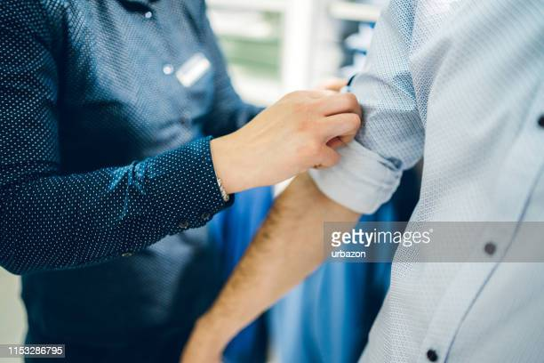 female seller helping man dress up - sleeve stock pictures, royalty-free photos & images