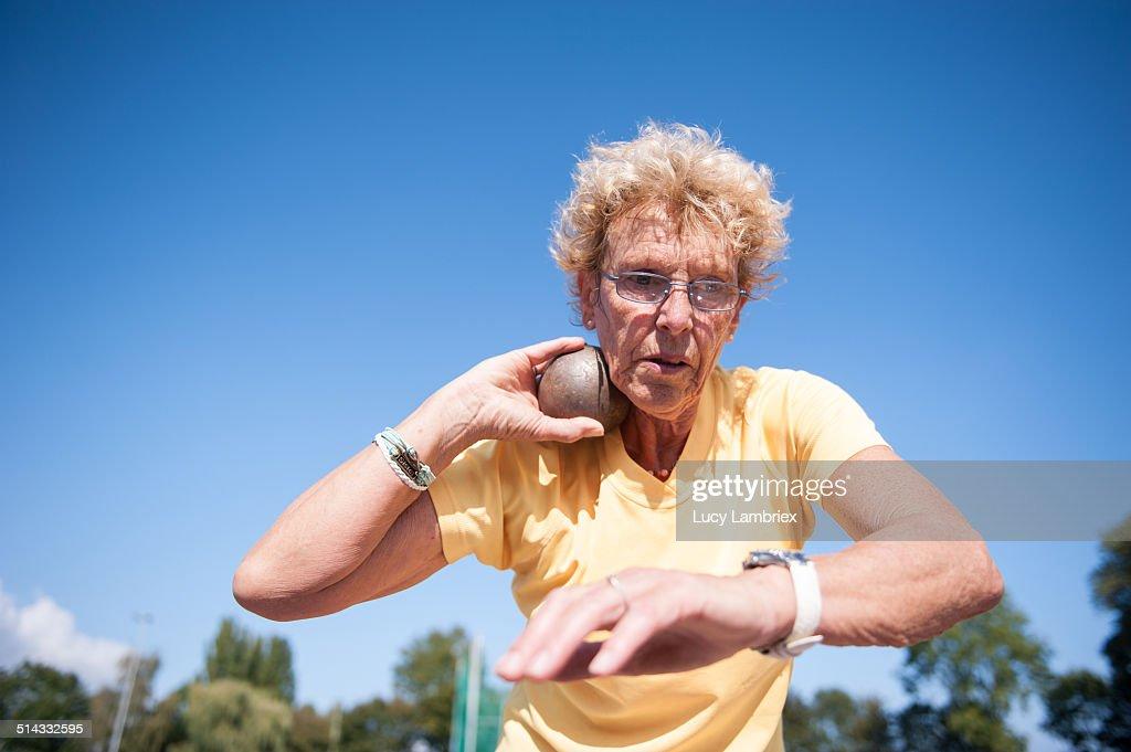 Female senior athlete (75) practicing shot put : Stock Photo