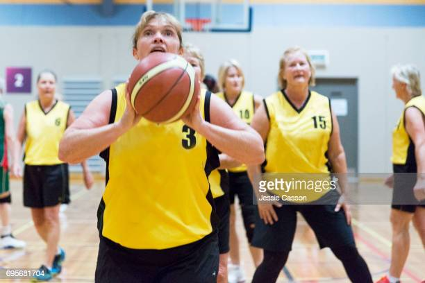 Female senior basketball players warming up on indoor court