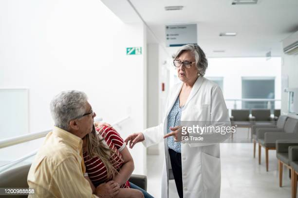 female senior doctor talking about bad news and consoling sad family at hospital - consoling stock pictures, royalty-free photos & images