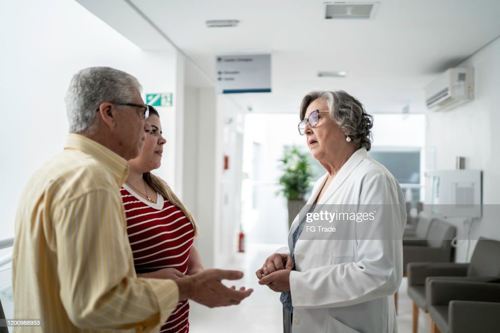 Female senior doctor talking about bad news and consoling sad family at hospital : Stock Photo