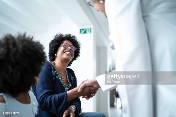 female senior doctor welcoming / greeting mother and daughter at hospital - visita imagens e fotografias de stock