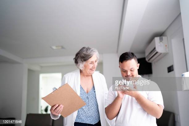 female senior doctor welcoming / greeting special needs boy at hospital - down syndrome stock pictures, royalty-free photos & images