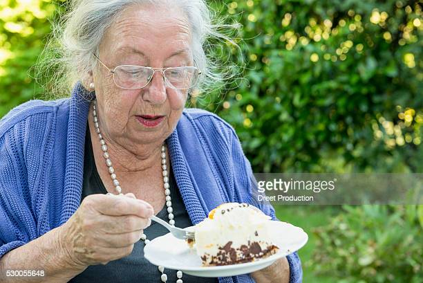 Female senior eating cream cake