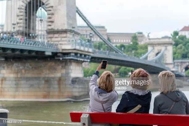 female senior friends exploring the city  on vacation - small group of people stock pictures, royalty-free photos & images