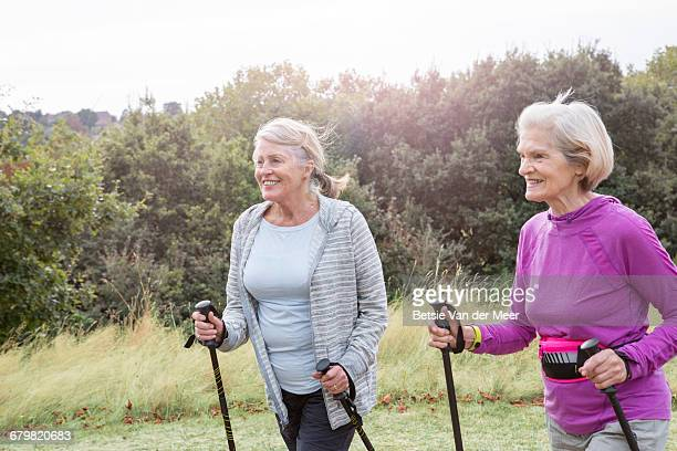 Female senior friends walking with nordic poles.