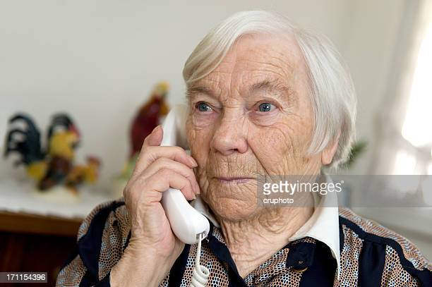 Female Senior is holding a phone and looks sad