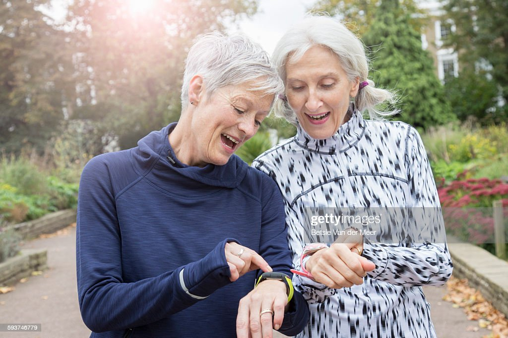 Female senior joggers checking fitness watches. : Stock Photo
