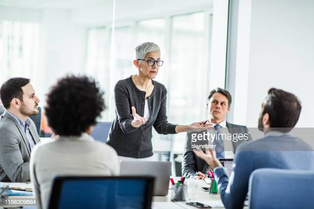 female senior leader arguing with her colleague on a meeting in the office. - smart casual stock pictures, royalty-free photos & images