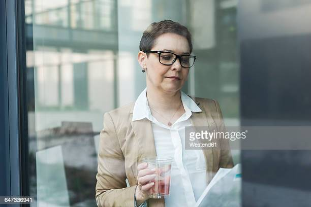 Female senior manager reading, holding a glass