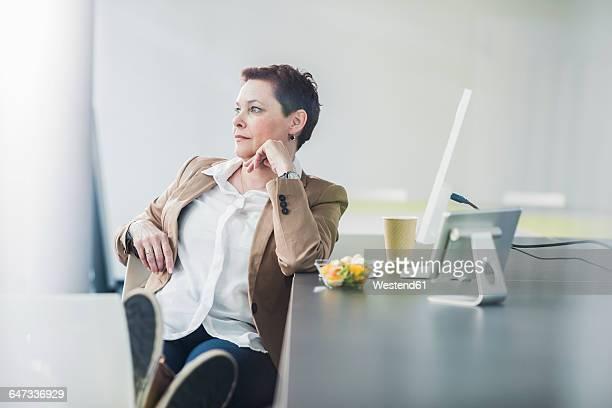 Female senior manager sitting in office, sideways glance