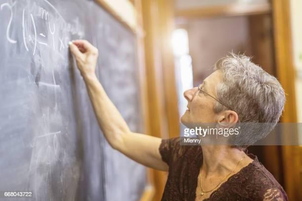 profesor de matemáticas senior femenino en el fórmula de la escritura de la pizarra - profesora mayor fotografías e imágenes de stock