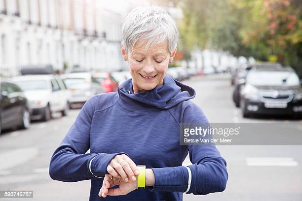 Female senior runner checks activity tracker.