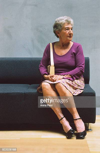female senior sitting on a sofa - older women in short skirts stock pictures, royalty-free photos & images