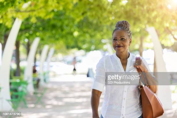 female senior tourist smiles as she walks through city park - black purse stock pictures, royalty-free photos & images
