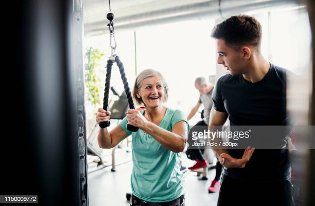 a female senior with a young trainer doing strength workout exercise in gym - core stock pictures, royalty-free photos & images