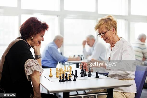 Female seniors playing chess in the community center