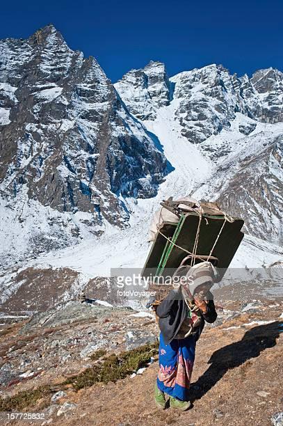 雌シェルパポーター重い負荷をヒマラヤ山脈ネパール山 - 職業 ポーター ストックフォトと画像