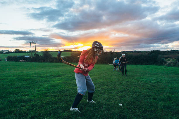 Female shinty player warming up at sunset