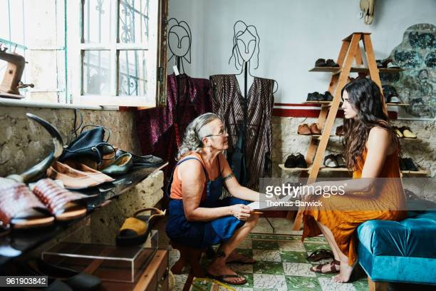female shoe maker taking custom order from client during fitting in boutique - mexican business women stock photos and pictures
