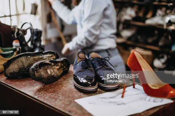 female shoemaker working at the shop - shoemaker stock photos and pictures