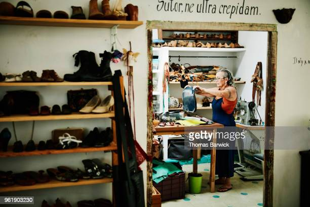 female shoemaker working with leather in workshop - shoemaker stock photos and pictures