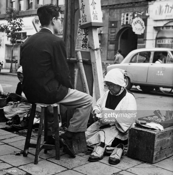 A female shoeshine in the Ginza district of Tokyo circa 1955