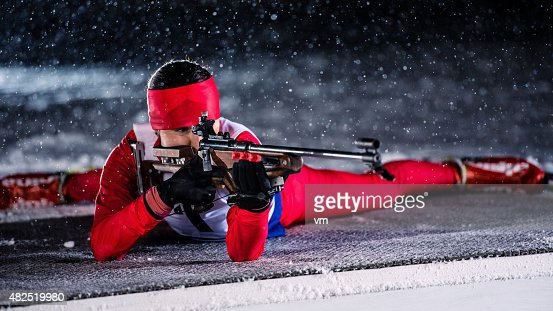 Female shooting at biathlon training at night