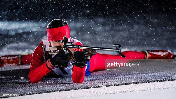 female shooting at biathlon training at night - langlaufen stockfoto's en -beelden