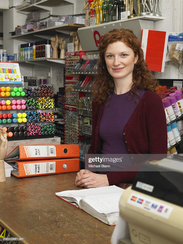 Female shop assistant behind counter in stationery shop, portrait : Stock Photo