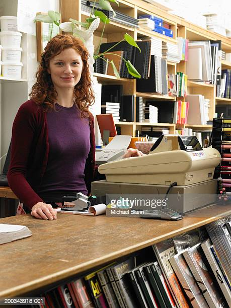 female shop assistant by cash register in art shop, smiling, portrait - book store stock photos and pictures