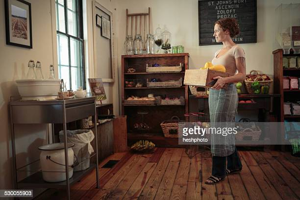 female shop assistant carrying fruit and veg crate in country store - heshphoto stock-fotos und bilder