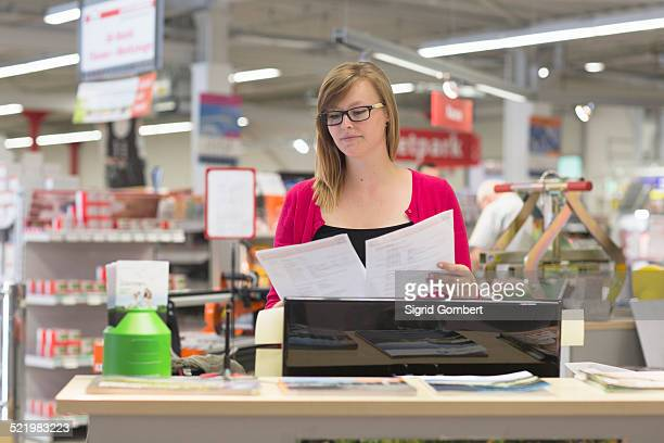 female shop assistant checking orders in hardware store - sigrid gombert stock pictures, royalty-free photos & images