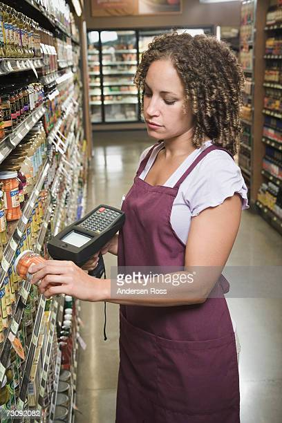 Female shop assistant checking product barcode in grocery store