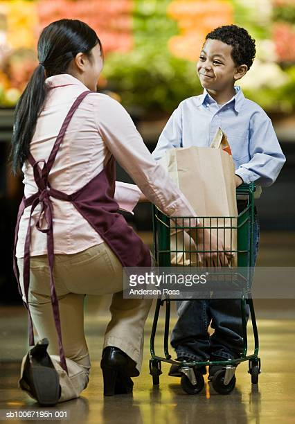 Female shop assistant helping boy (8-9) in supermarket