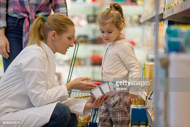 Female shop assistant helping girl in supermarket