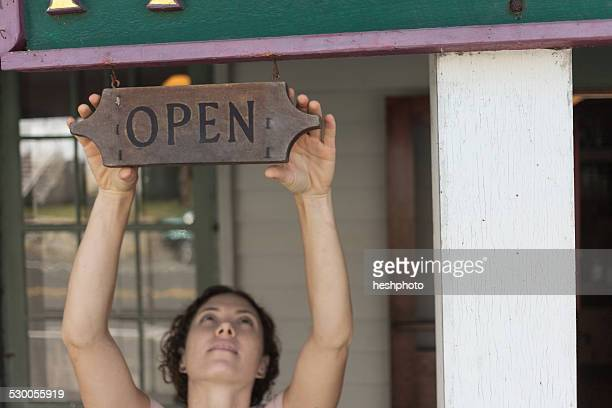 female shop assistant reaching for open sign at country store - heshphoto stock pictures, royalty-free photos & images