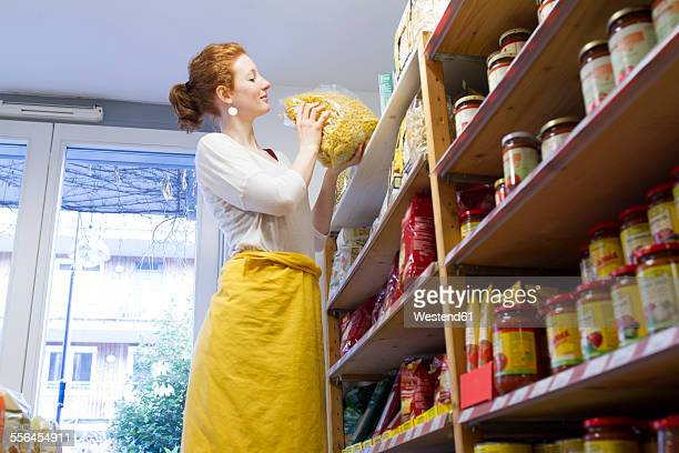 Female shop assistant sorting merchandise in wholefood shop