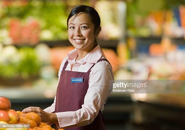 Female shop assistant standing in supermarket, smiling, portrait