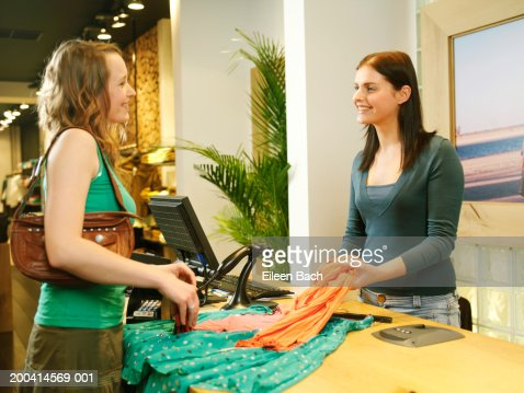 Female Shop Assistant Taking Clothes From Woman At Counter