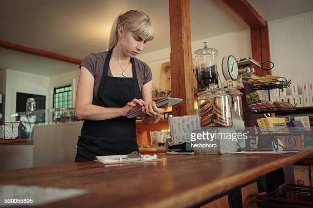 female shop assistant using touchscreen on digital tablet in country store - heshphoto stock pictures, royalty-free photos & images