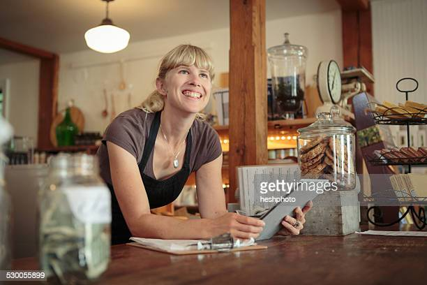 Female shop assistant with digital tablet in country store