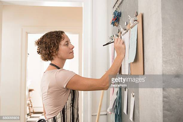 female shop assistant writing on wall clipboards in kitchen at country store - heshphoto stock-fotos und bilder
